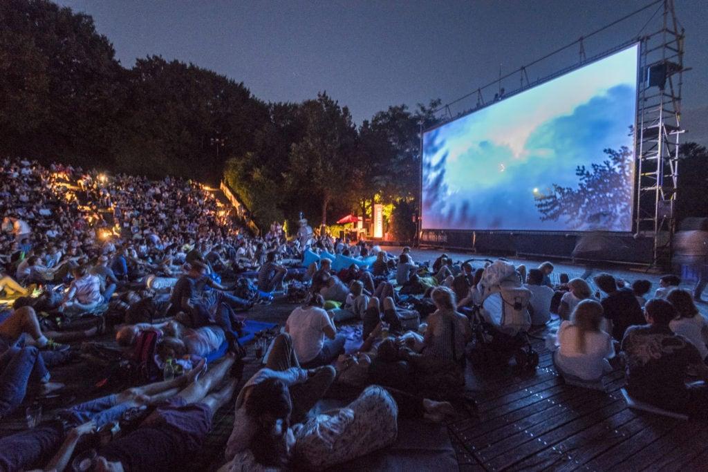 Menschen im Open-Air-Kino in München mit leuchtender Leinwand