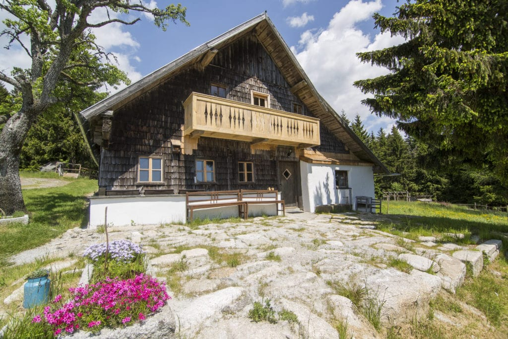 Rustikaler Bauernhof in Bayern im Wald an einem sonnigen Tag.