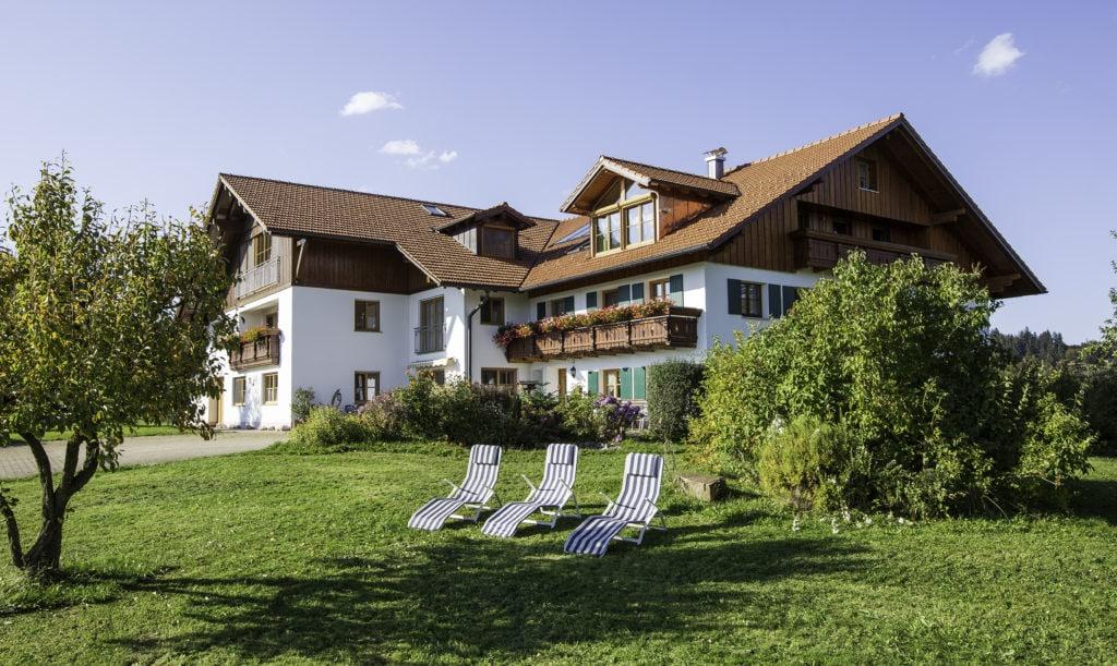 Drei Liegen auf einer Wiese vor einem schicken Ferienhof in Bayern.