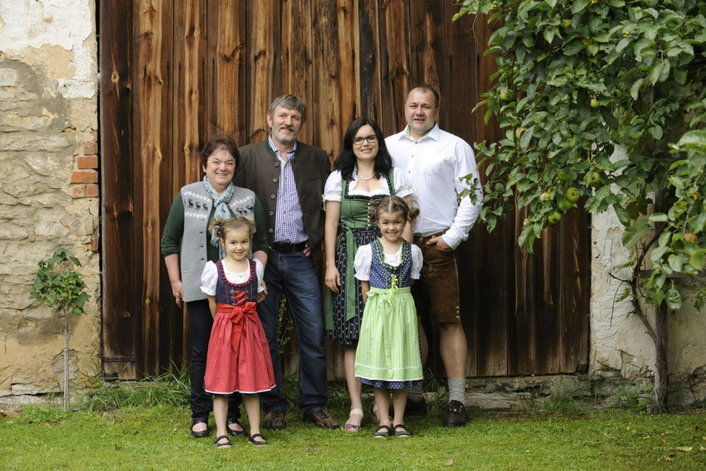 Familie Schmidtner steht in traditionell bayrischen Trachten vor einem hölzernen Tor. Sie betreiben einen familienfreundlichen Bauernhof in Bayern.