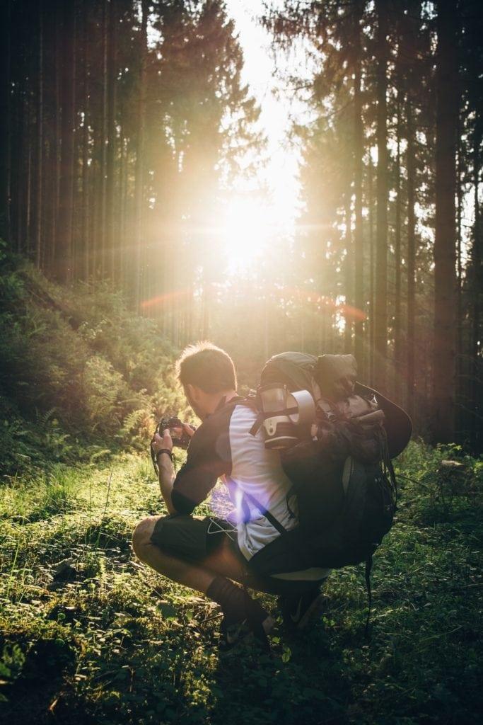 Mann hockt im Wald und schaut auf seine Kamera