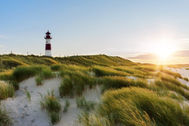 Lighthouse on Sylt, one of the most famous islands in Germany, in front of green dunes in the evening sun
