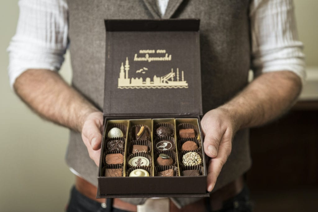 Ein Mann hält eine Schachtel Pralinen mit einer Auswahl an verschiedenen Sorten