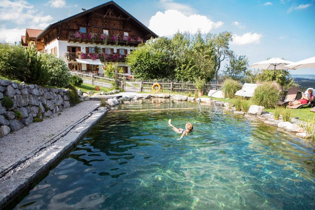 Eine Frau die im Pool vor einem Ferienhaus in Bayern schwimmt