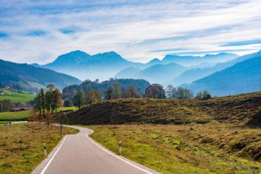Kurvige Strasse im Bergtal im Herbst. Landschaftliche Ansicht der Fahrbahn, sanft abfallende Hügel, Wiesen mit gelbem Gras, goldenem Sonnenlicht und malerischen Bergen im Hintergrund laden zu einem Roadtrip durch Deutschland ein