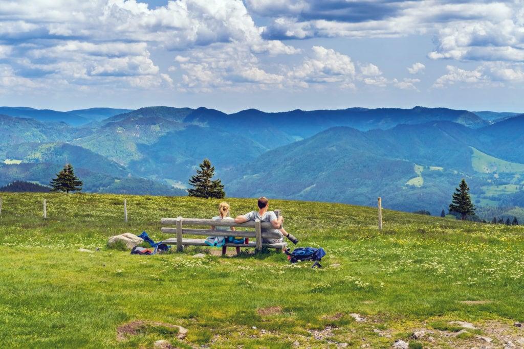 Pärchen sitzt auf einer Parkbank und genießt die Aussicht auf den Schwarzwald