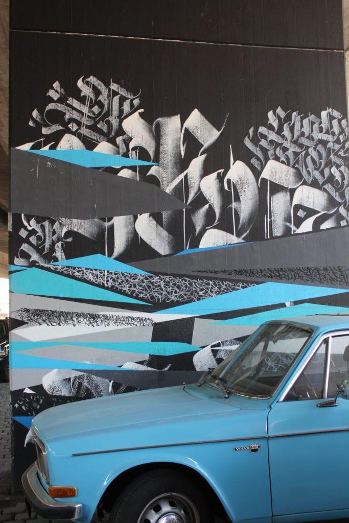 Ein blaues Auto steht vor einer Wand mit Street Art