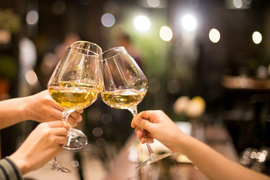 Menschen stoßen mit Weißwein an. In Deutschland trinkt man gerne Riesling oder Grauburgunder.