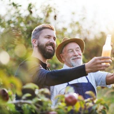 Zwei Männer halten ein Glas gegen die Sonne