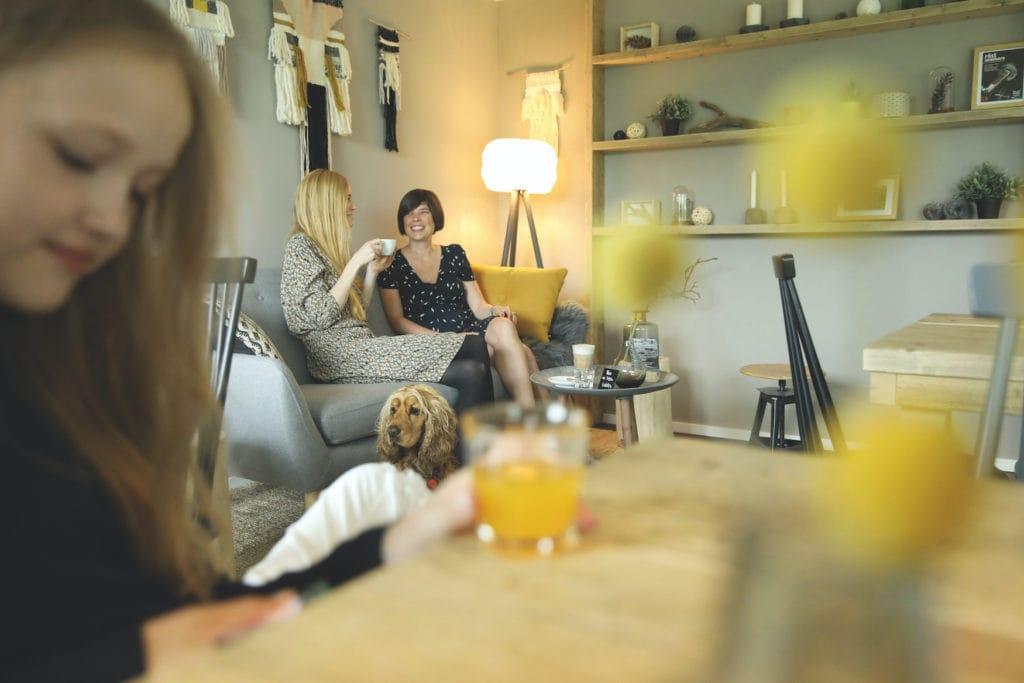 Zwei Frauen sitzen auf einer Couch im Cafe und plauschen, während ein anderer weiblicher Gast vorne liest