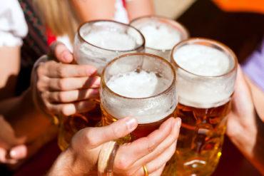 Menschen die mit einem Bierkrug anstoßen in Biergarten in Augsburg