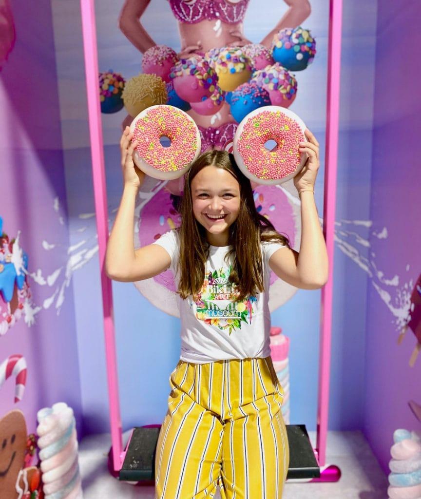 Mädchen posiert mit zwei Kunststoff-Donuts auf Schaukel