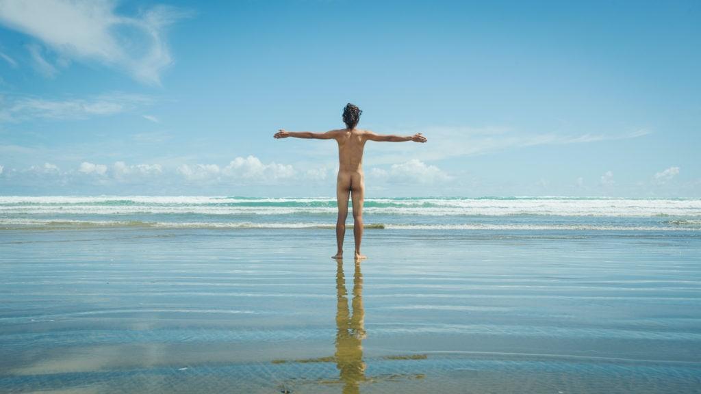 Nackter Mann steht mit ausgebreiteten Armen am Strand