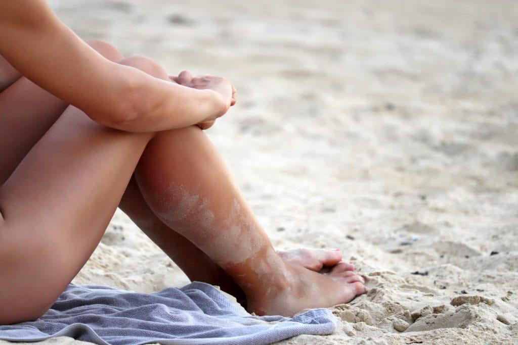 Frau sitzt mit aufgestellten Beinen an Strand in Deutschland