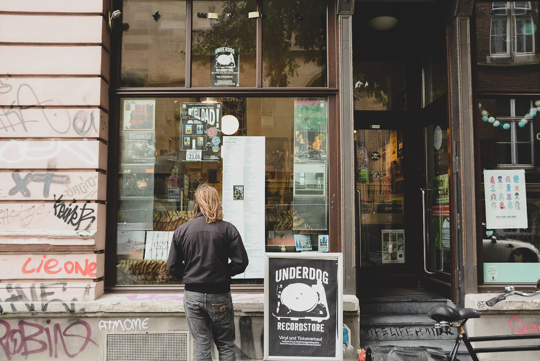 Mann steht vor Underdog Schallplattenladen in Köln und betrachtet das Schaufenster