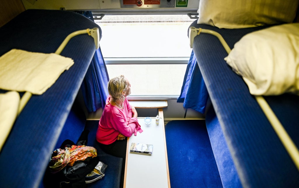 A woman waiting for the departure of the train in a compartment of the new Alpen-Sylt-Nachtexpress from Sylt to Salzburg
