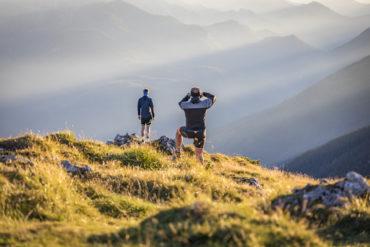 Zwei Männer sind auf Berg im Berchtesgadener Land gewandert und genießen die Aussicht
