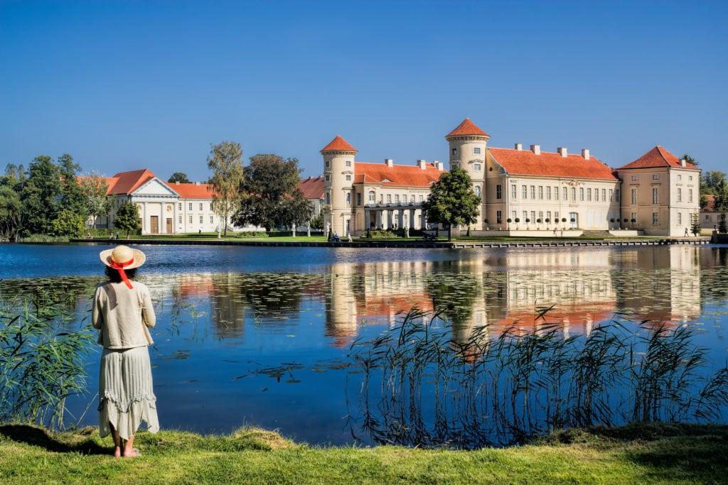 Frau posiert vor See, im Hintergrund sieht man das Schloss Rheinsberg