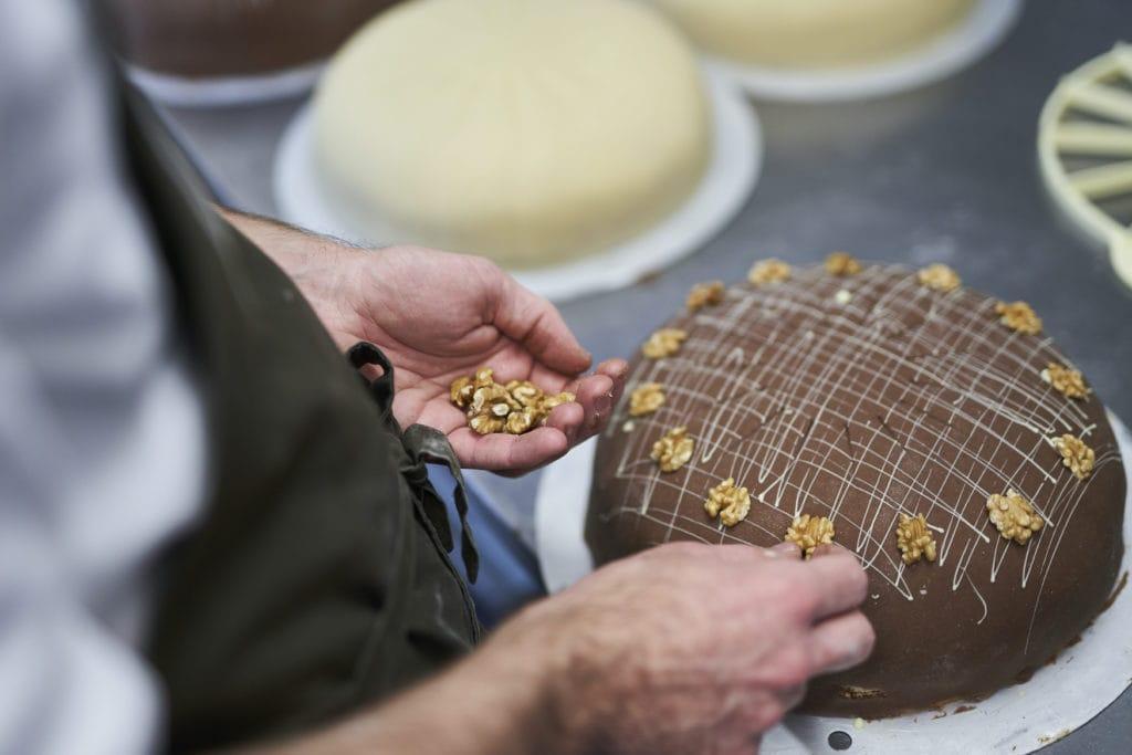 Konditor verziert Schokoladen-Torte mit Walnüssen