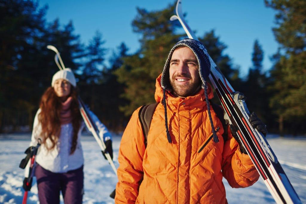 Pärchen mit Langlauf-Skiern in verschneiter Landschaft
