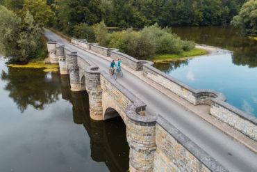 Frau und Mann radeln über Brücke im Sauerland
