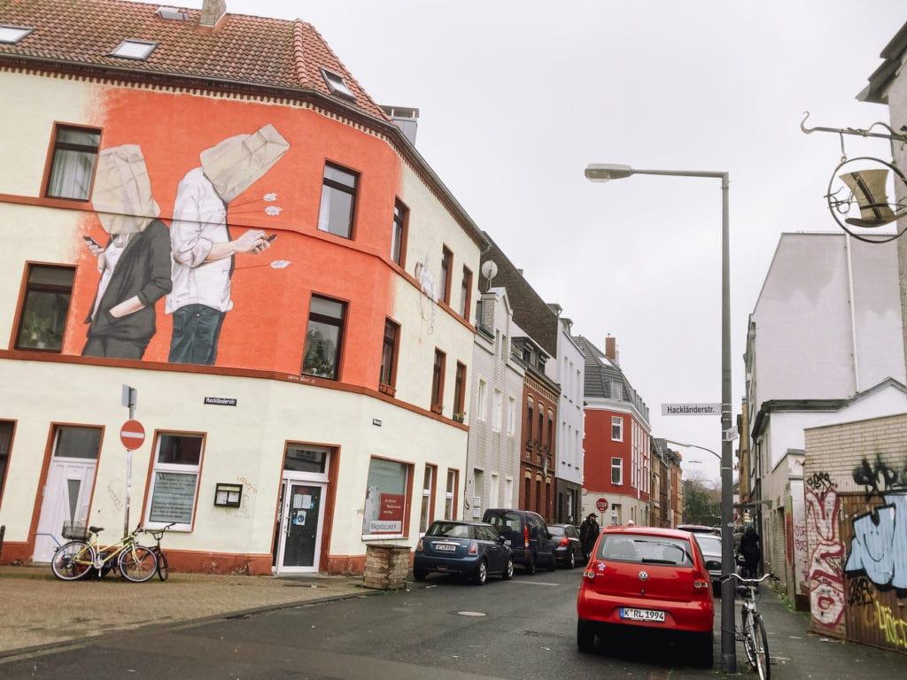 """Zwei Menschen mit Papiertüten stehen Rücken an Rücken und starren auf ihr Handy, Amorpfeile stecken in ihrem Bauch. Street Art Werk von """"Mr. Trash"""""""