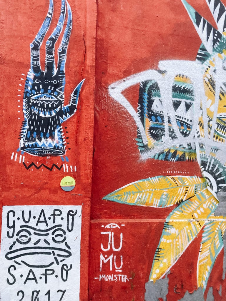 Verschiedene Graffitis an roter Hauswand