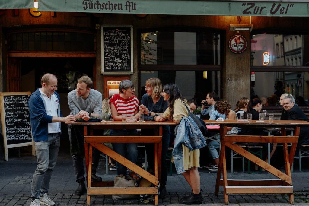 Gruppe von menschen sitzt in der Düsseldorfer Altstadt an einem Tisch vor einer Brauerei