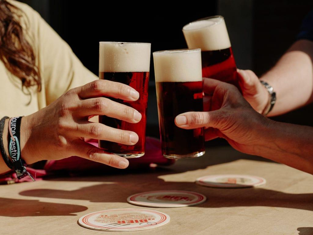 Menschen stoßen mit Alt, eine Biersorte aus NRW, an