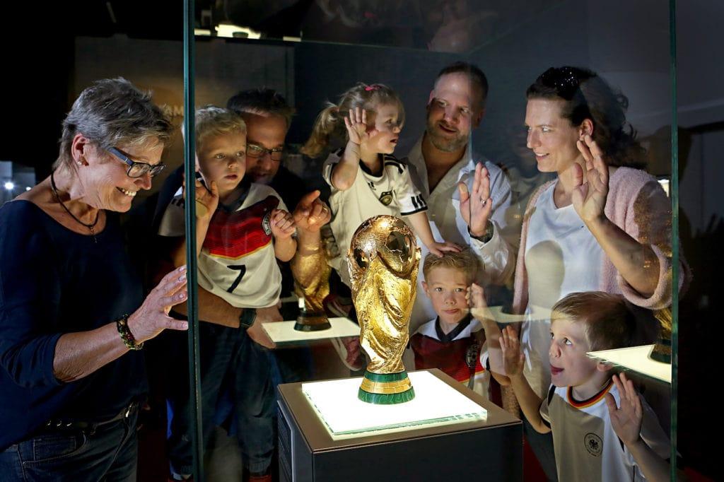 Museumsbesucher stehen an Vitrine und schauen sich Siegerpokal der Fußballweltmeisterschaft an