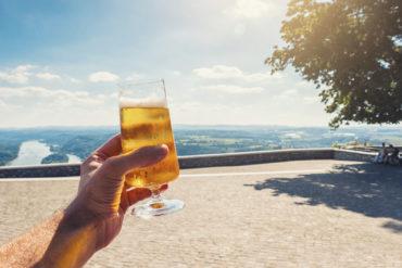 Junger Mann hält Glas mit Bier in die Kamera vor sonnigen Aussichten