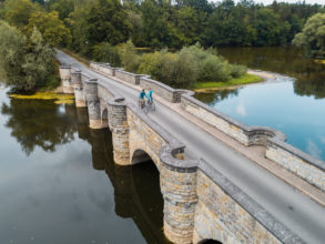 Woman and man cycling over bridge in Sauerland region, Western Germany