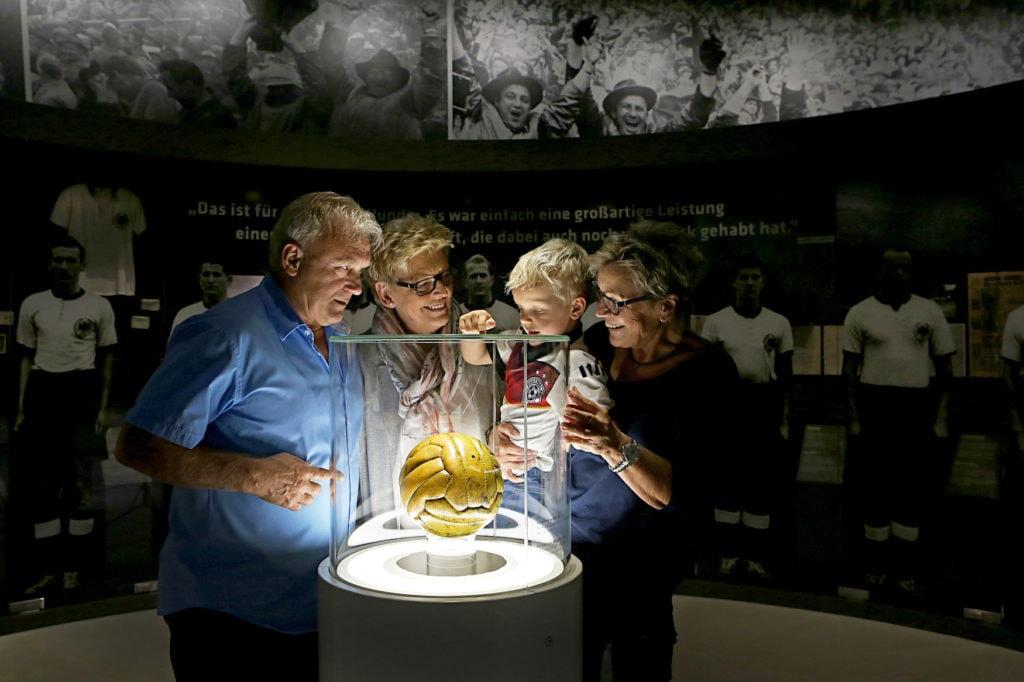 Familie schaut sich goldenen Fußball in Museum an