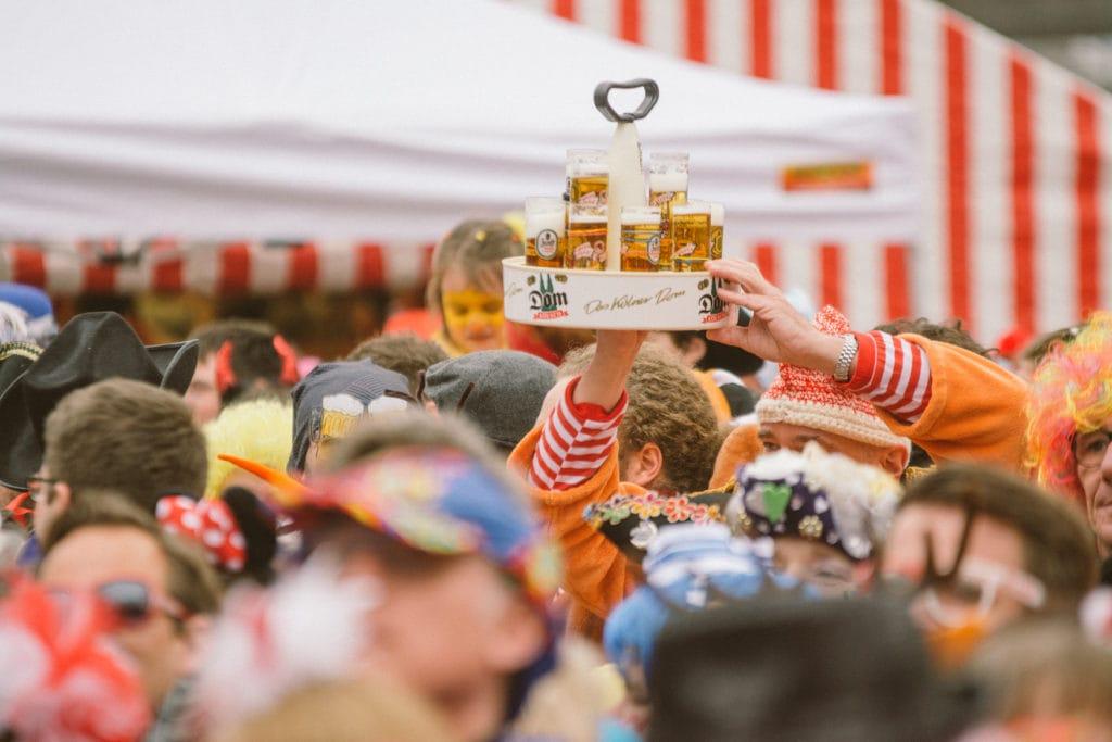 Bier wird durch die Menschenmenge vor Kölner Kneipe gereicht