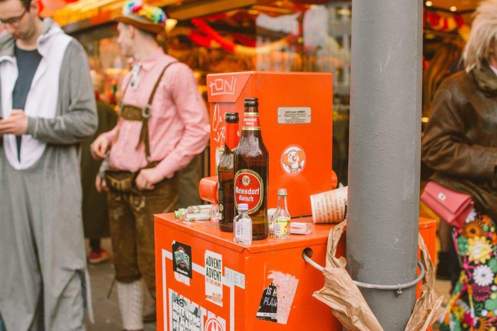 Kölschflaschen stehen auf Zeitungsautomat in Kölner Südstadt während Karneval
