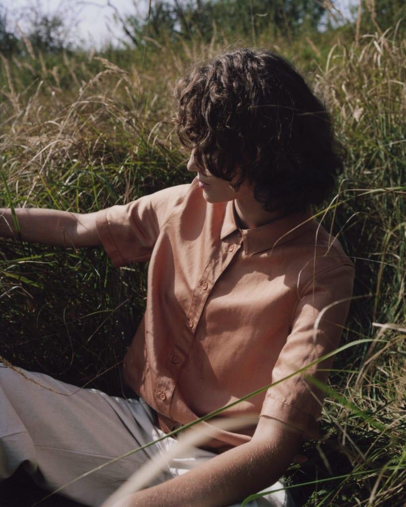 Junges Model liegt in Gras und trägt Pfirsich-farbene Bluse von Armedangels