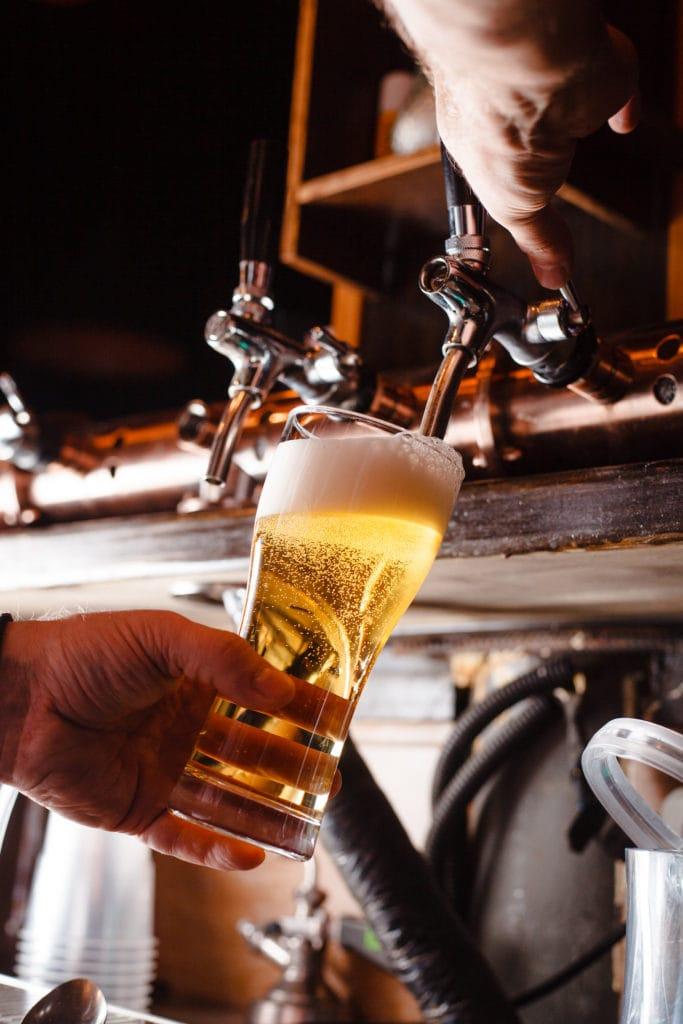 Wirt zapft Bier in Kneipe in NRW
