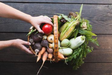 Frau nimmt Tomate aus Korb voller Gemüse