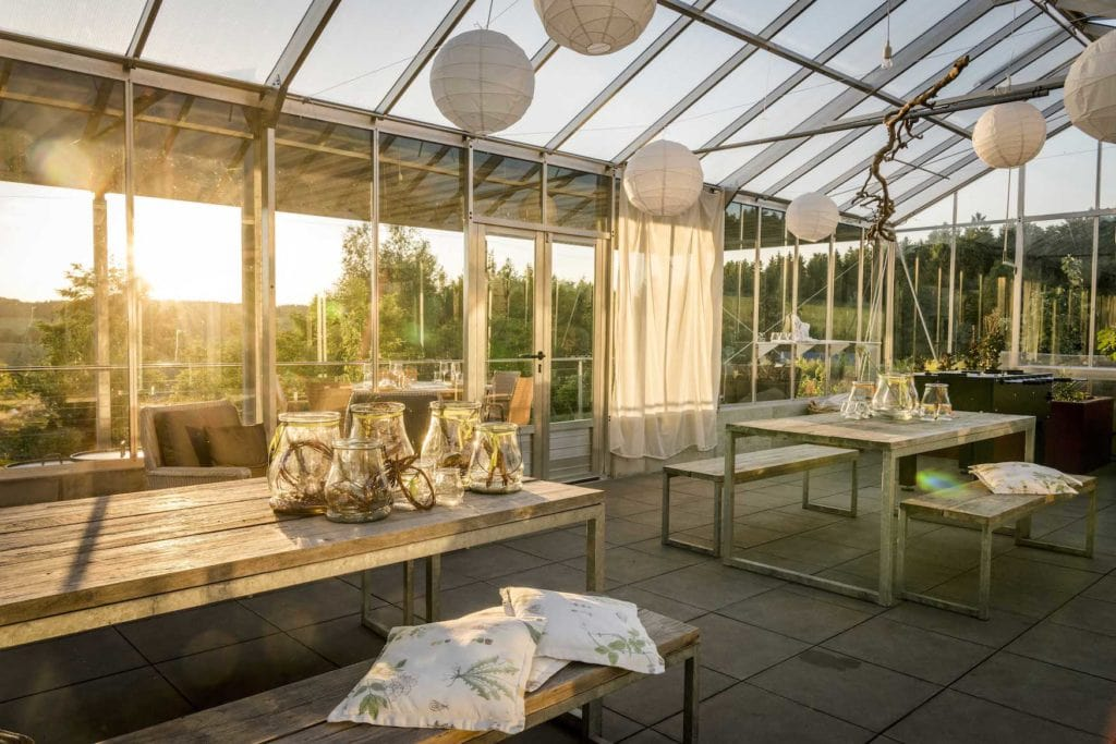 Glashaus mit schöner Dekoration spiegelt im Sonnenlicht