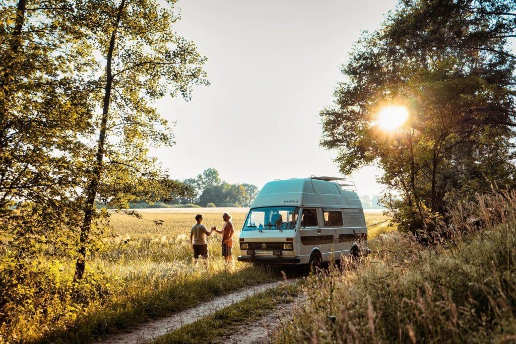 Camper steht in deutscher Natur bei Sonnenuntergang