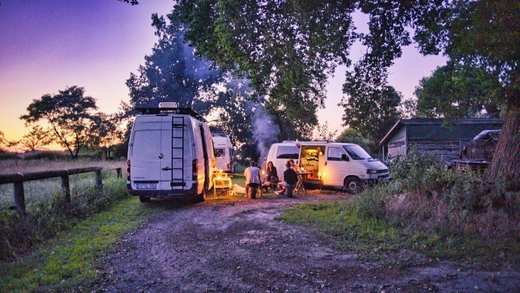 Menschen machen ein Lagerfeuer vor ihren Wohnmobilen auf einem Bauernhof in Deutschland, gebucht haben sie den Stellplatz über Stadt Land Bus Camping