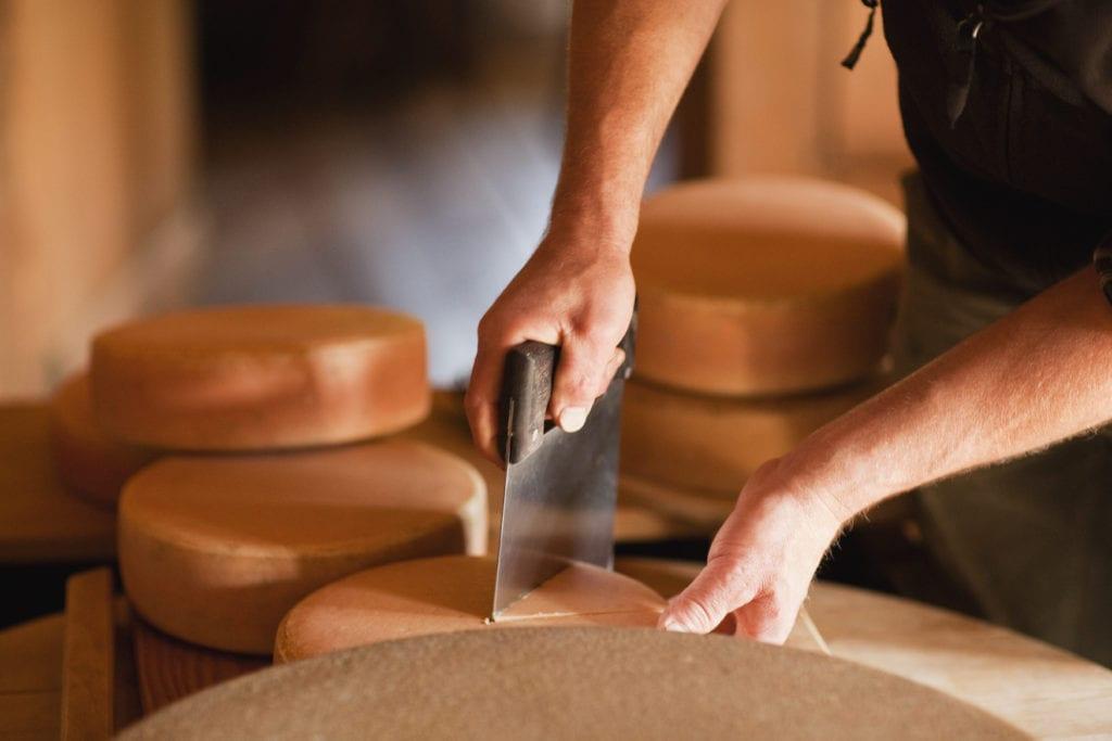 Mann schneidet Käse-Laib