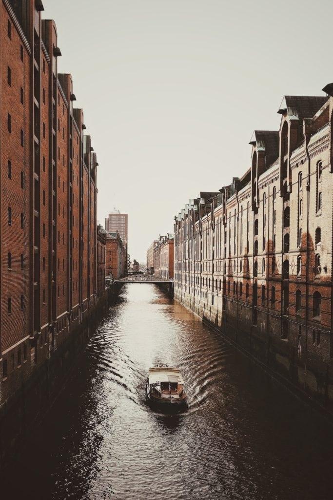 Blick auf ein Boot das durch die Kanäle der Speicherstadt fährt
