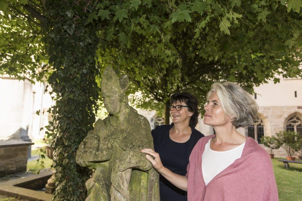 Zwei Frauen schauen sich Skulpturen im Kreuzganggarten an