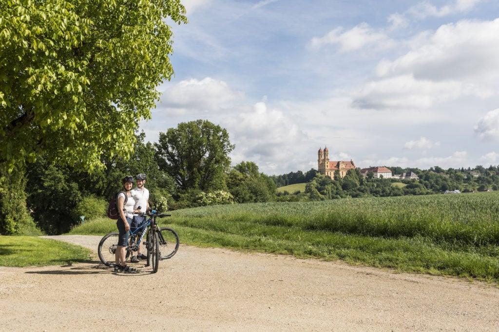 Fahrradfahrer auf dem Kocher-Jagst-Radweg mit der Schönenbergkirche im Hintergrund