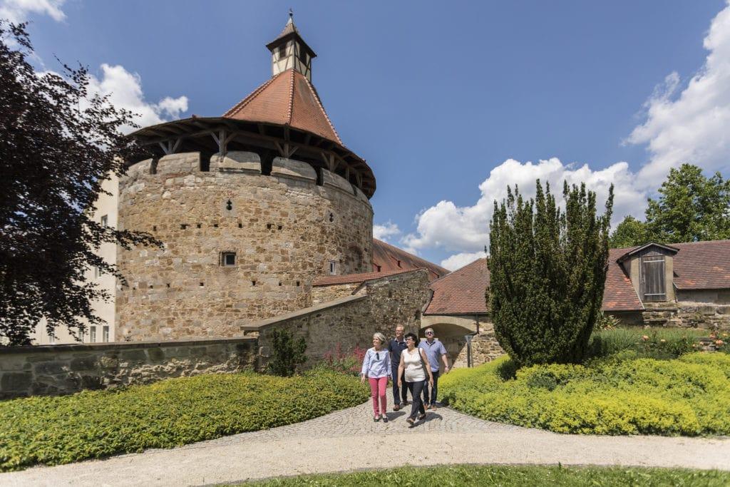 Zwei ältere Pärchen spazieren durch den Basteigarten am Schloss Ellwangen