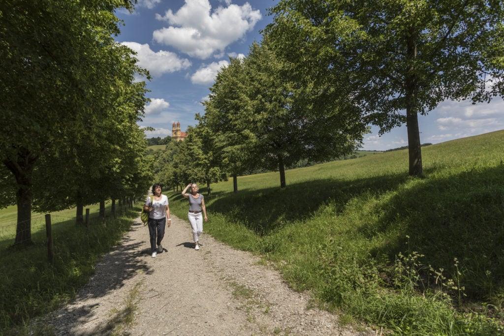 Zwei Frauen mittleren Alters wandern vorm Schloss in Ellwangen durch die Natur
