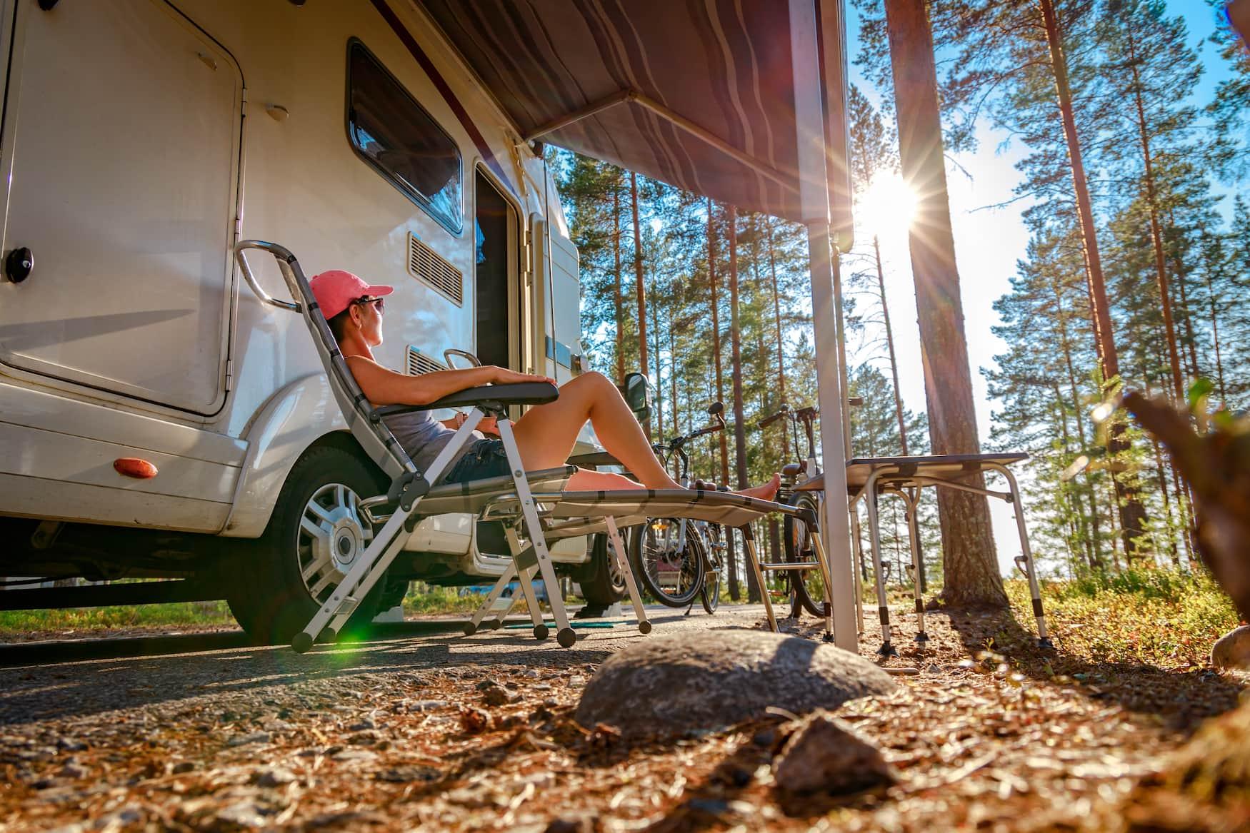 Frau sitzt auf Campingstuhl vor ihrem Wohnmobil auf einem Campingplatz