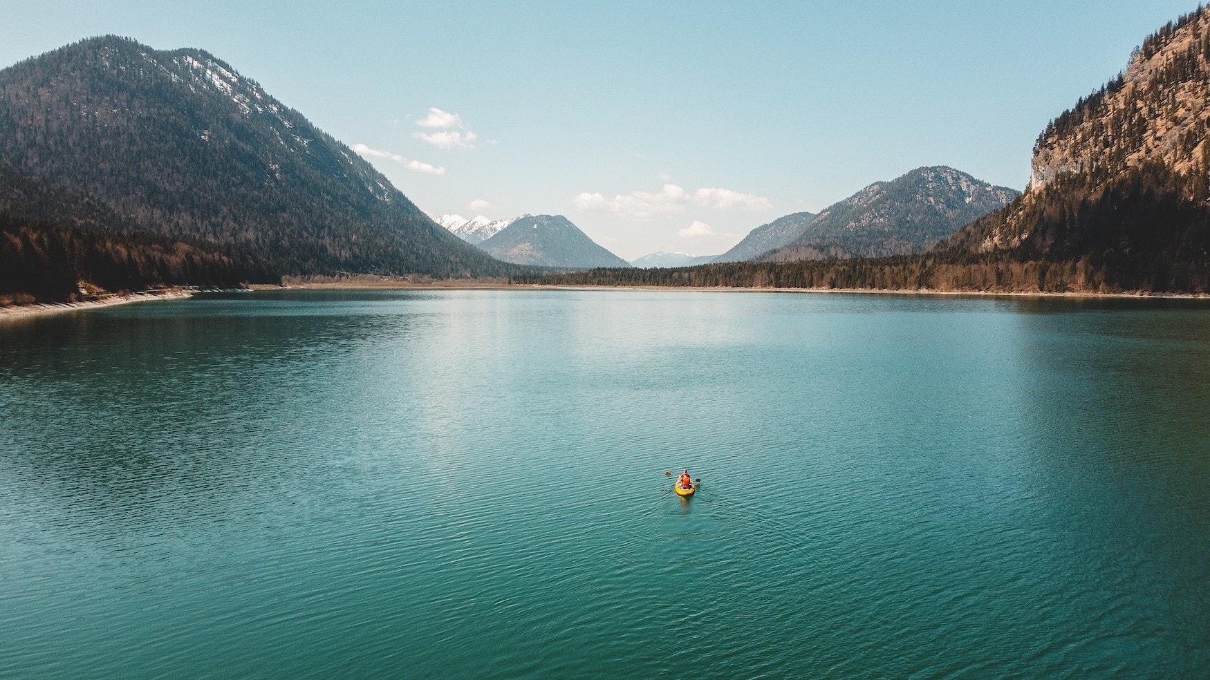 Frau ist in Kayak auf einem See in Deutschland vor Bergkulisse