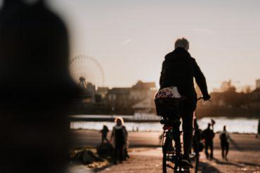 Fahrradfahrerin vor der Rheinkulisse in Köln